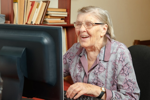 Пожилая женщина изучает компьютер и смотрит интернет