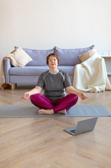 年配の女性は、ラップトップモニターの前の蓮華座で自宅で瞑想します。老後の健康的でアクティブなライフスタイルの概念。縦の写真。