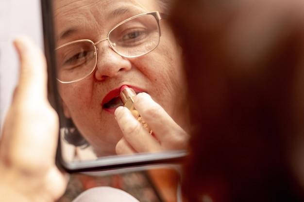 나이든 여성은 립스틱으로 입술을 칠하고 아름다움을 돌봅니다. 진지한 할머니는 거울 앞에서 립스틱을 바르세요. 거울에 비친 여성의 모습