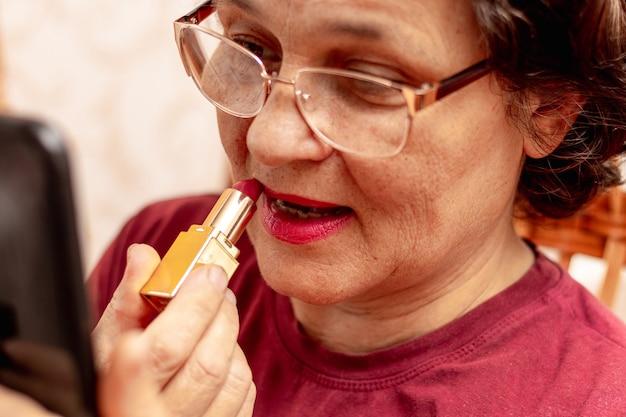 나이든 여성은 립스틱으로 입술을 칠하고 아름다움을 돌봅니다. 거울 앞에서 립스틱을 바르는 진지한 할머니