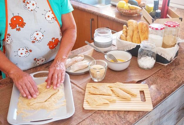 年配の女性は、フィッシュアンドチップス用に卵とパン粉を使って魚の切り身を準備します。キッチンテーブル