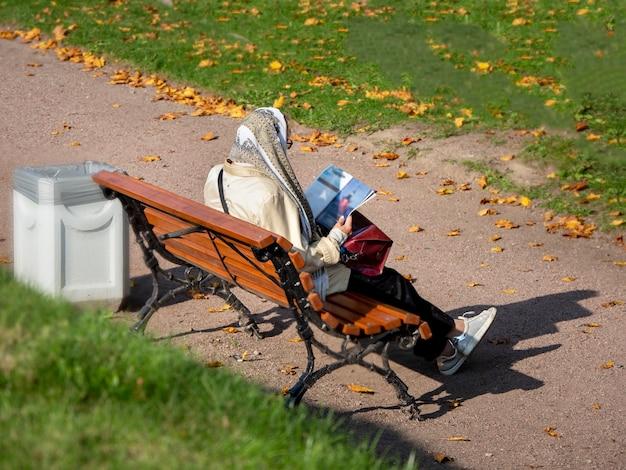 ある年配の女性が、秋の都市公園に背を向けてベンチに座って読んでいます。