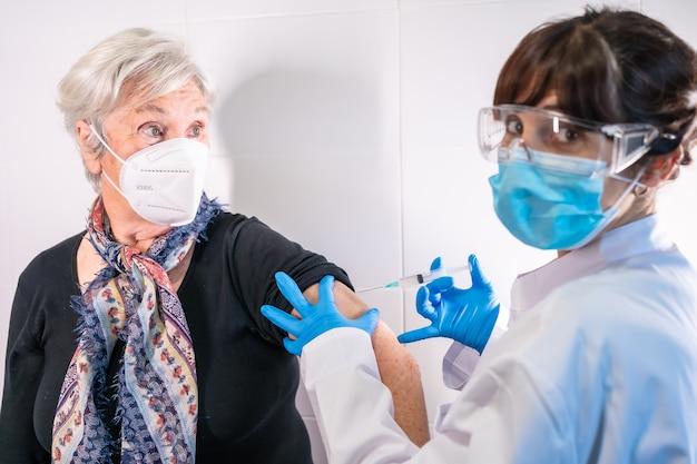 의사가 코로나 바이러스 백신 주사를 맞은 노인 여성. 항체는 인구를 면역화합니다.