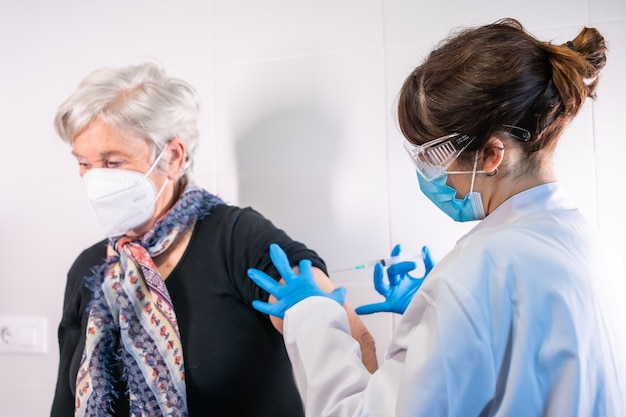 항체를 받기 위해 의사가 코로나 바이러스 백신 주사를 맞은 노인 여성이 인구를 예방합니다.
