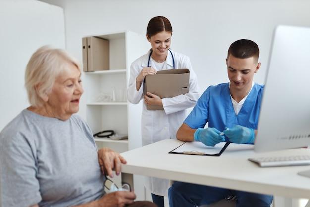 Пожилая женщина сидит на приеме у врача с медсестрой
