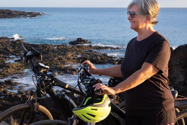 노인 여성이 자전거를 타고 절벽에 멈춥니다. 그녀 옆에 두 대의 전기 자전거가 있습니다. 배경에 푸른 바다 물입니다. 일몰 빛