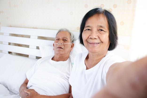 寝室のベッドで肺疾患と呼吸器疾患に苦しんでいる夫と一緒に写真を撮る年配の女性。コロナウイルスのケア、励まし、予防の概念