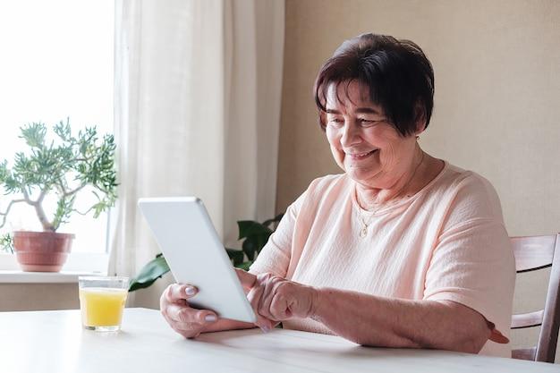 Пожилая женщина пользуется планшетом дома и смотрит контент в социальных сетях