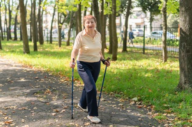 화창한 여름날 공원에서 노인 여성이 막대기로 북유럽을 걷습니다.