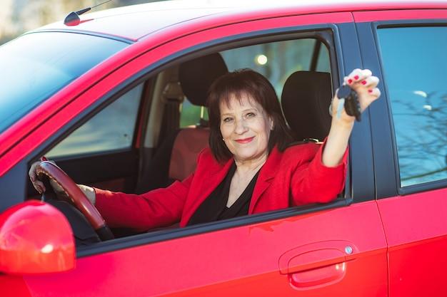 年配の女性に赤い車が贈られました。おばあちゃんは鍵と笑顔を持っています