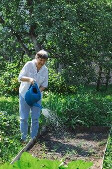 정원에 있는 식물에 물을 주는 할머니