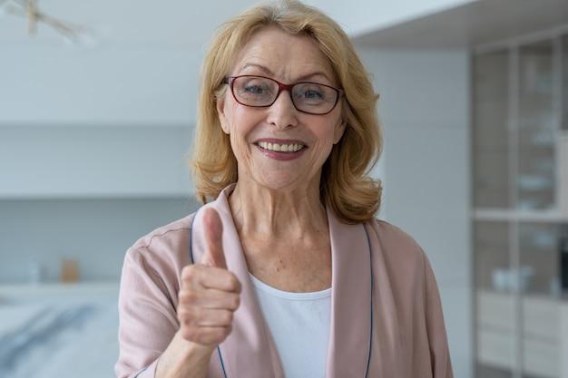 眼鏡をかけた年配の女性が親指をあきらめてカメラを見る