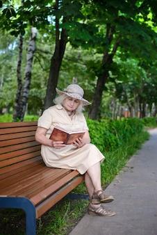 Пожилая женщина с седыми волосами в шляпе и бежевом платье сидит на скамейке в парке и читает книгу