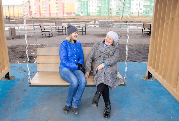 그녀의 딸과 함께 노인 여성이 그네에 앉아 이야기하고 웃고 사람들이 의사 소통합니다