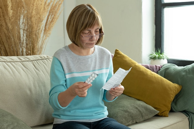 약을 든 노인 여성이 집에서 소파에 앉아 지침을 읽습니다.