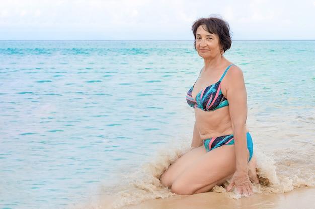 カメラ目線と笑顔の水着で年配の女性女性