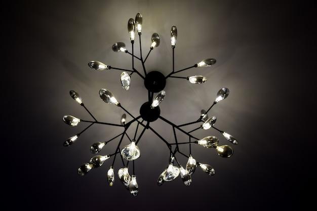 В сумерках на потолке висит электрическая люстра с множеством ярких светящихся лампочек.