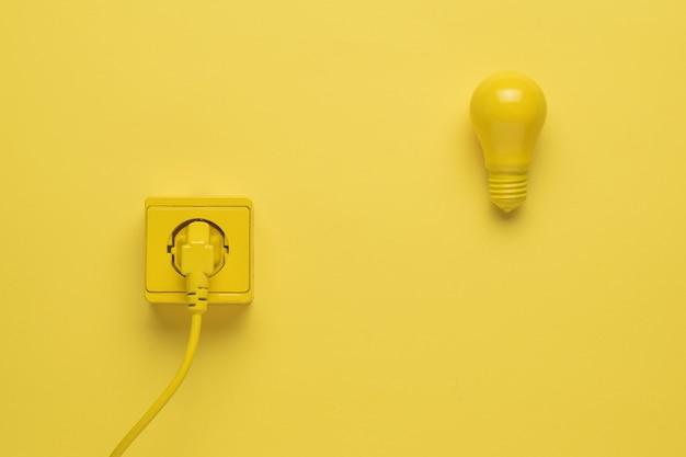 콘센트에 삽입된 전기 코드와 노란색 배경에 전구.