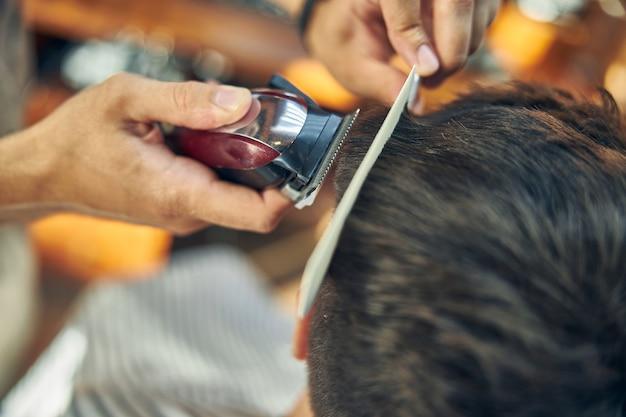 理髪店の訪問者の髪をカットしてスタイリングするために使用されている電気トリマー