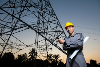 An electrical engineer wearing yellow hat hold black mobile phone at electricity power pol