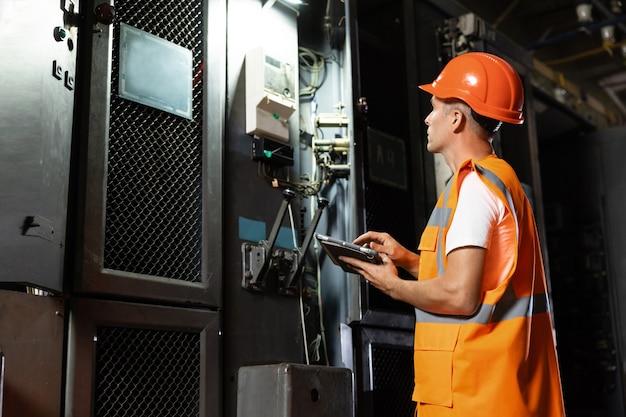 Инженер-электротехник в каске и жилете подходит к стойке и использует цифровой планшет.