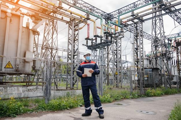 전기 변전소 엔지니어가 범 혈병 당시 마스크에있는 최신 고전압 장비를 검사합니다.