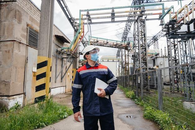 変電所のエンジニアは、池血症の際にマスク内の最新の高電圧機器を検査します。エネルギー。業界。