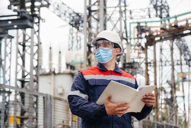 전기 변전소 엔지니어는 족병시에 마스크로 현대식 고전압 장비를 검사합니다. 에너지. 산업.