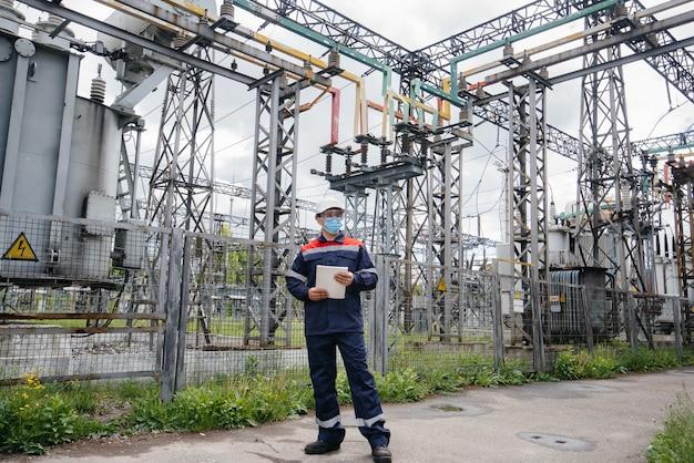 変電所のエンジニアは、流行の際にマスク内の最新の高圧機器を検査します。エネルギー。業界。