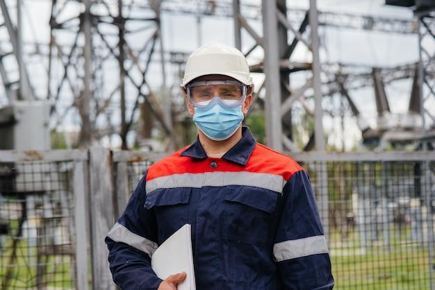変電所のエンジニアは、ポンデミア時にマスク内の最新の高電圧機器を検査します。エネルギー。業界。