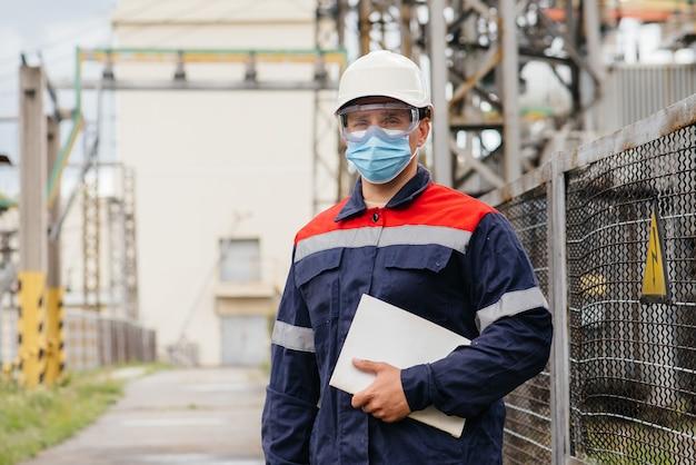 Инженер электрической подстанции осматривает современное высоковольтное оборудование в маске во время пондемии. энергия. промышленность.