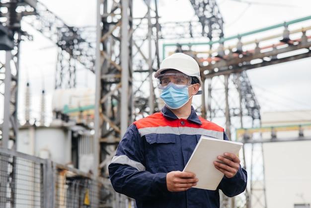 Инженер электрической подстанции осматривает современное высоковольтное оборудование в маске