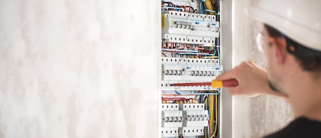 Электротехник, работающий в распределительном щите с предохранителями