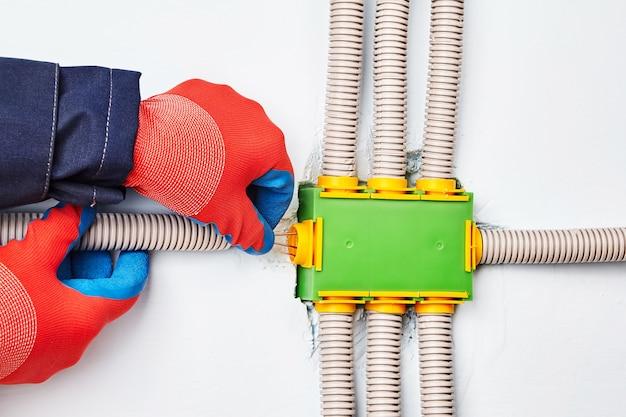 Электрик подключает электрический кабель к распределительной коробке квадратной формы из зеленого пластика с восемью выводами.