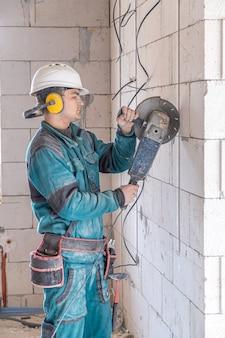 Электрик-строитель в защитном шлеме на рабочем месте работает с болгаркой.