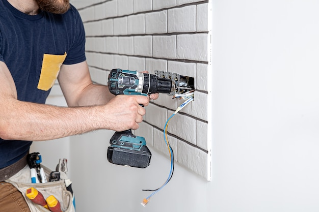 Электрик-строитель в комбинезоне с дрелью во время установки розеток. концепция ремонта дома.