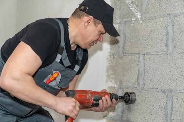 電気技師は、穴あけ器の特別なノズルを使用して、コンセント用の壁に穴を開けます