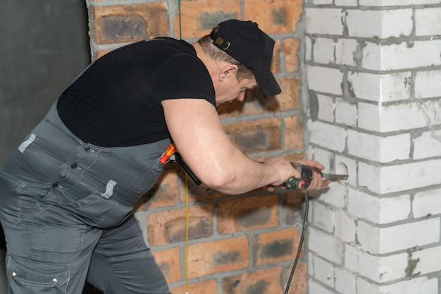 전기 기사가 천공기의 특수 노즐을 사용하여 콘센트 용 벽에 구멍을 뚫습니다.
