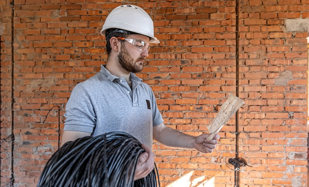 Электрик изучает строительный чертеж, держа в руке электрический кабель на рабочем месте.