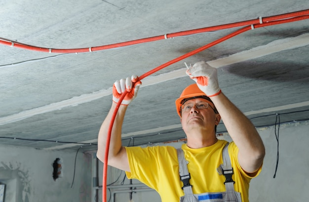 Электрик крепит гофрированную электрическую трубу к потолку