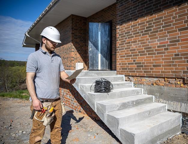 Электрик держит в руках строительный чертеж и осматривает рабочий объект.