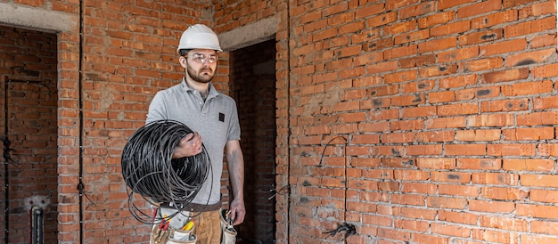 Электрик в каске смотрит в стену, держа в руке электрический кабель.