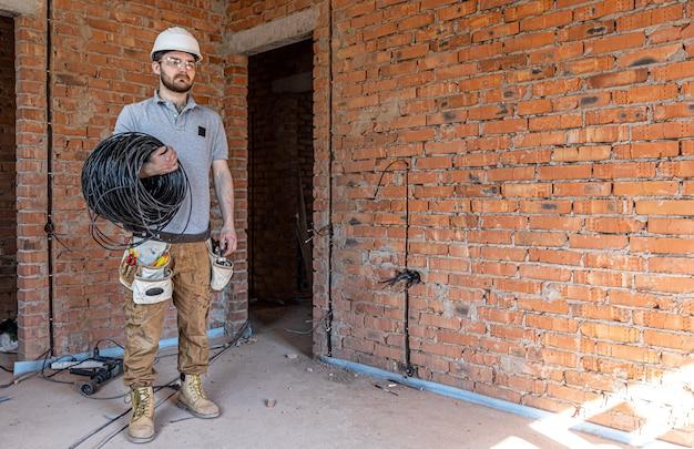 Электрик в каске смотрит в стену, держа в руке электрический кабель