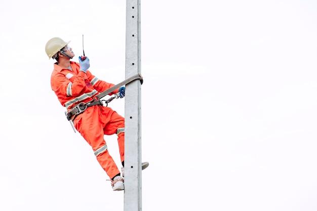 안전 복을 입은 전기 기사가 전등 기둥을 오르고 있습니다.