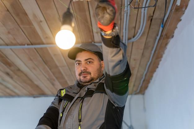 Электрик в комбинезоне смотрит на включенный патрон лампочки, с которым он держит