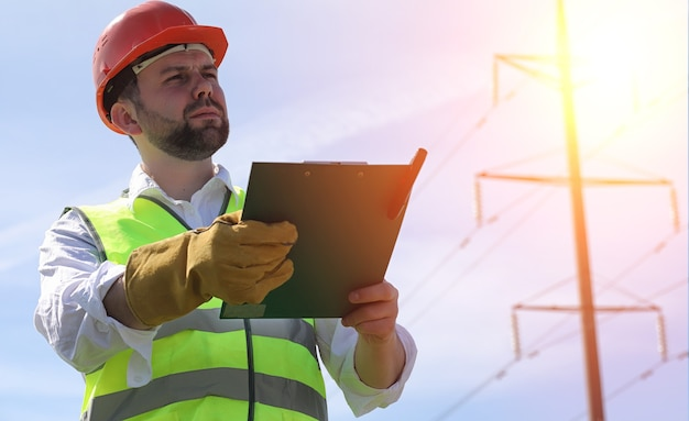 송전선로 근처 들판의 전기공. 전기 기술자는 전력선을 세우는 과정을 관리합니다. 헬멧과 반사 형태의 정비공과 직장에서 특수 장갑.