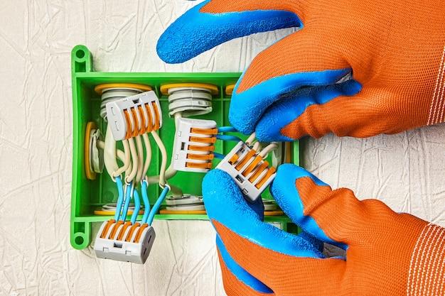 전기 기술자가 커넥터 단자에 도체를 삽입합니다. 전선을 삽입할 때