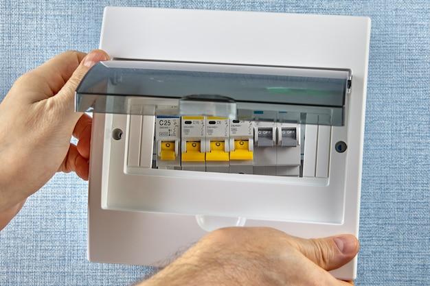 Электрик устанавливает пластиковую крышку на новый электрический шкаф.