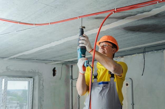 Электрик сверлит потолок перфоратором, чтобы закрепить гофротрубу