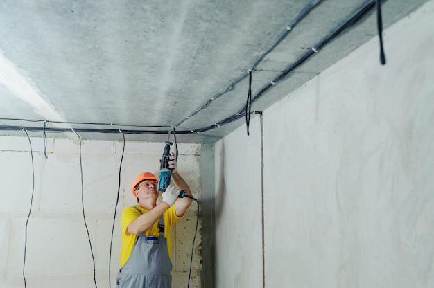 전기 기사가 천공기로 천장을 뚫고 있습니다.